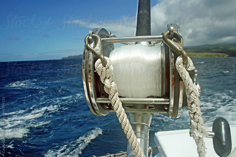 View of a large fishing reel on the end of a boat by Carolyn Lagattuta for Stocksy United