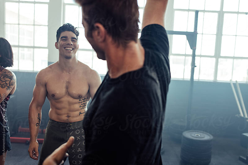 Muscular man smiling with friends working out at gym by Jacob Ammentorp Lund for Stocksy United