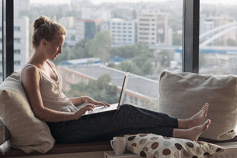 woman with laptop by the window  by RG&B Images for Stocksy United