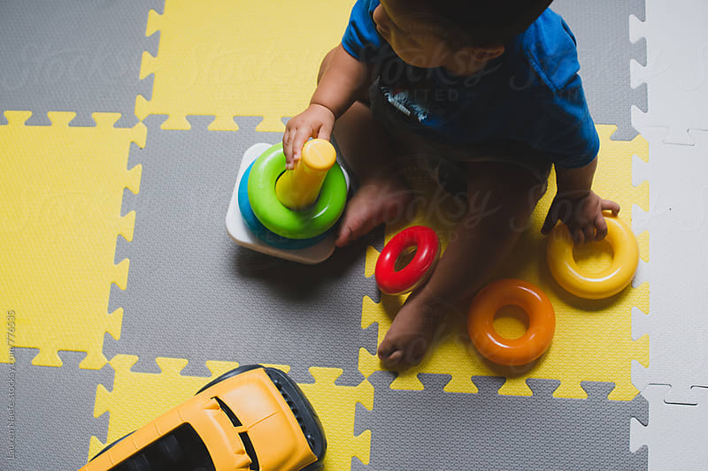 Toddler playing with rings by Lauren Naefe for Stocksy United