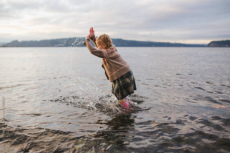 Side View of Little Girl Standing and splashing in Water fully dressed for fall by Amanda Voelker for Stocksy United