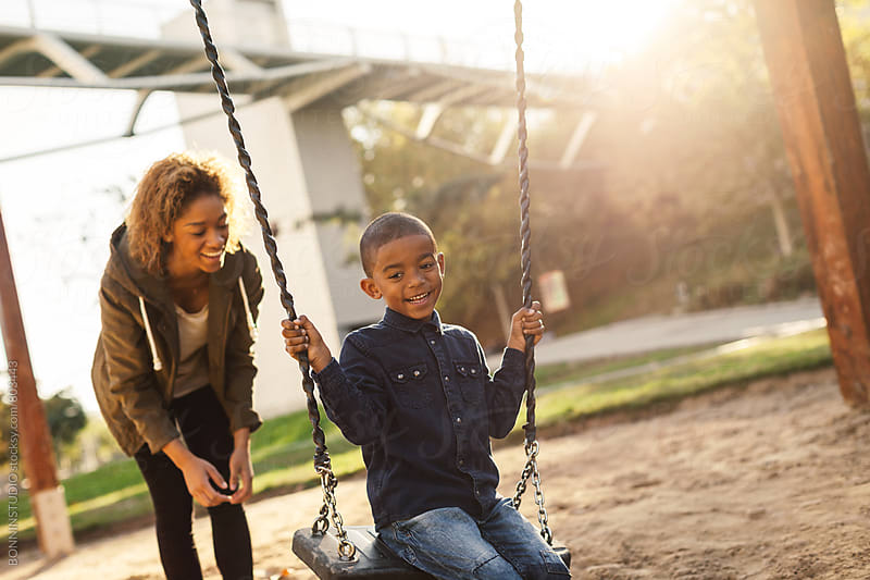 Black mother and her son having fun on playground swing. by BONNINSTUDIO for Stocksy United