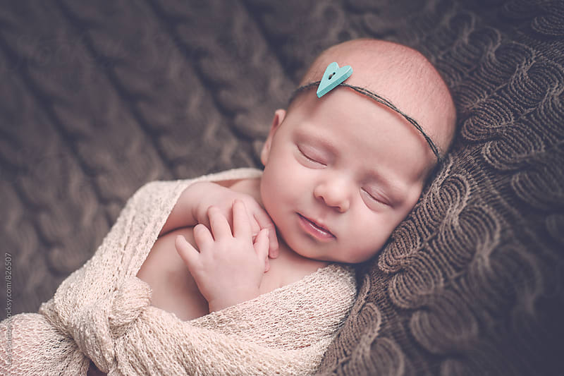 Beautiful newborn baby girl sleeping peacefully on a blanket by Lea Csontos for Stocksy United