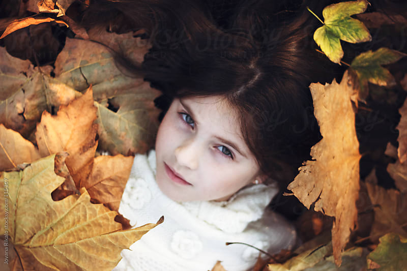 Portrait of a cute little girl surrounded by leaves by Jovana Rikalo for Stocksy United