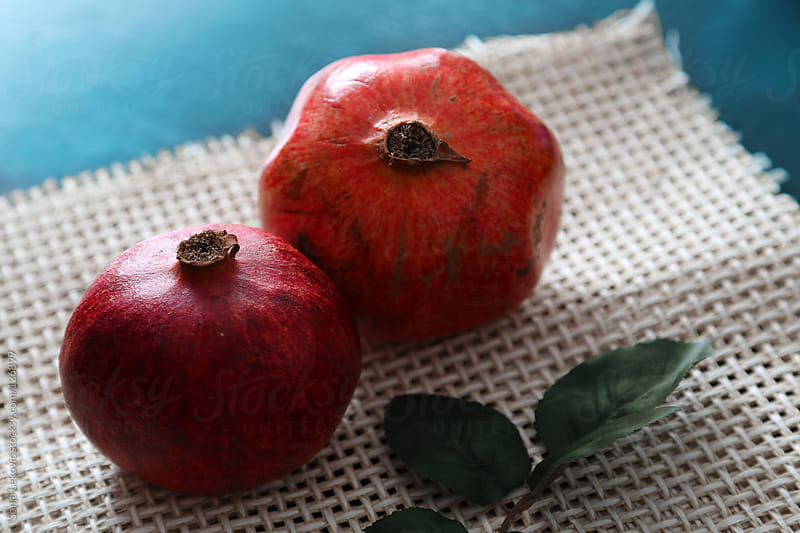 two pomegranates by Sonja Lekovic for Stocksy United