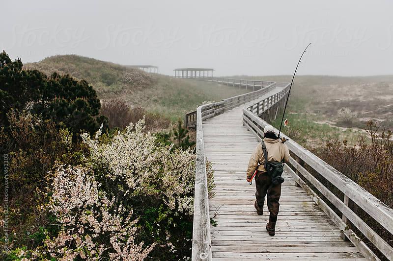 Senior Man Walking down boardwalk with Fishing Rod by Raymond Forbes LLC for Stocksy United