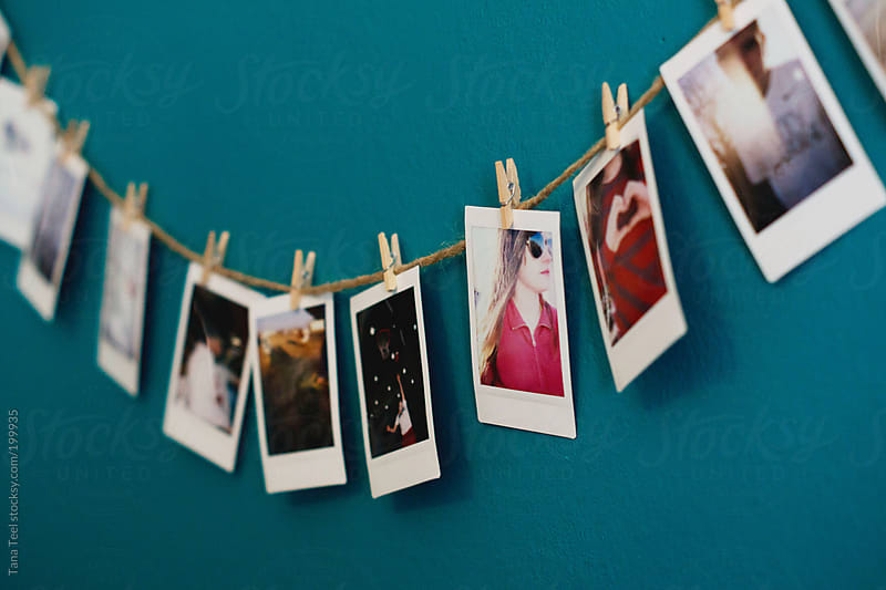 A side view of a string of mini polaroids hanging on a wall by Tana Teel for Stocksy United