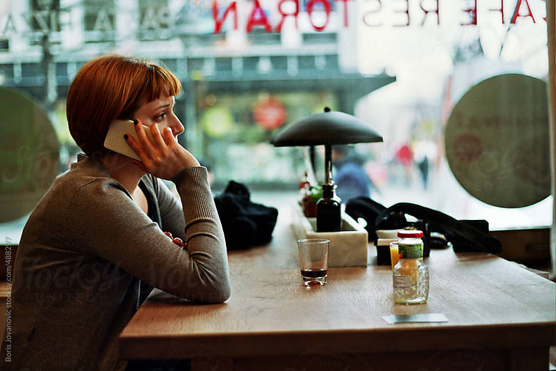 Young ginger woman talking on phone in restaurant by Boris Jovanovic for Stocksy United