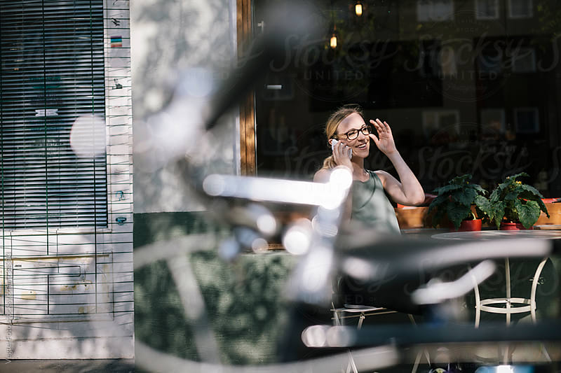 Woman talking on Cell phone at a Cafe by VegterFoto for Stocksy United