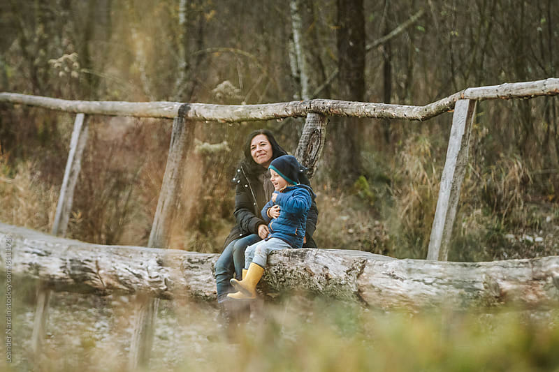 mother and her son sitting on a wooden bridge in a forest having fun by Leander Nardin for Stocksy United
