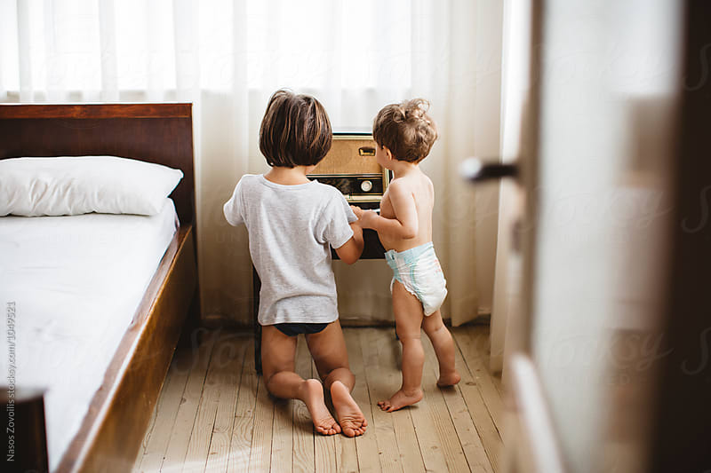 Kids playing with a vintage radio by Nasos Zovoilis for Stocksy United