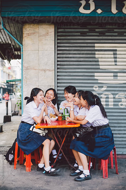 Thai high school girls in student uniform sitting at street restaurant in Bangkok by Nabi Tang for Stocksy United
