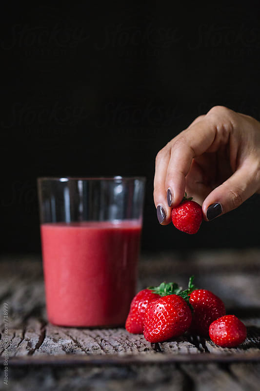 Woman holding strawberry next red smoothie on wooden table by Alberto Bogo for Stocksy United