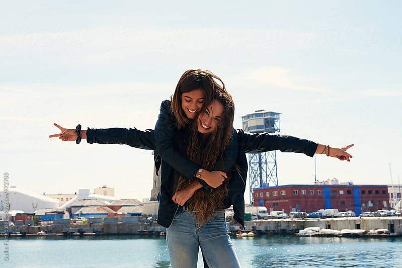 Two young girlfriends on pier  by Guille Faingold for Stocksy United