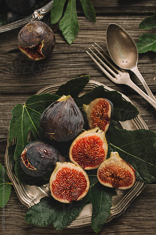 Fresh figs on wooden table by Blai Baules for Stocksy United
