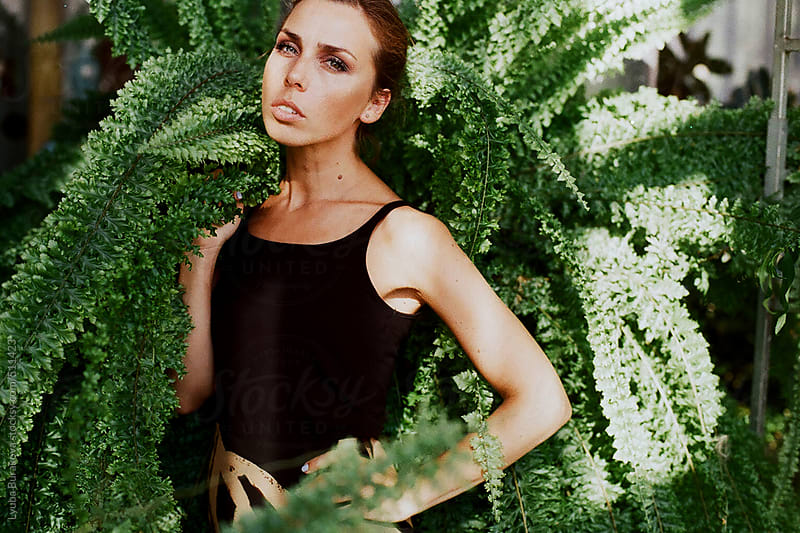 Portrait of the woman in fern looking at camera by Lyuba Burakova for Stocksy United