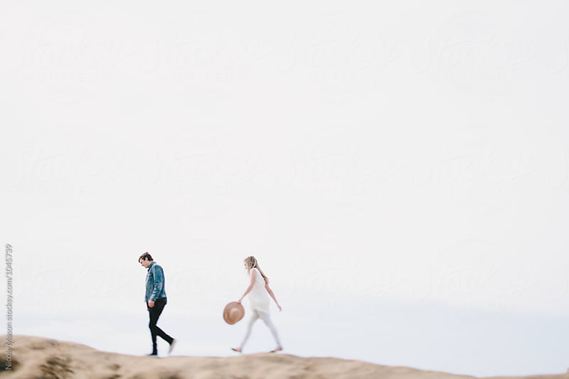 young couple walking separately along top of sand dune by Nicole Mason for Stocksy United
