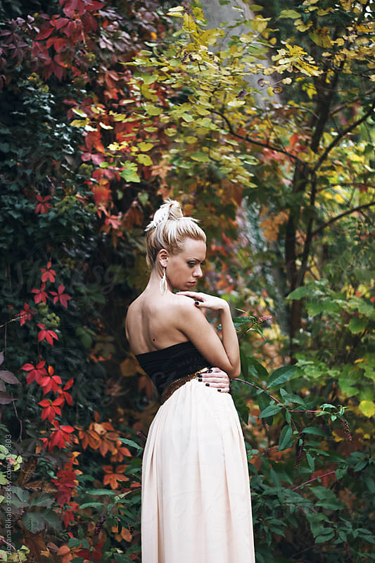 Beautiful girl standing in colorful autumn leaves by Jovana Rikalo for Stocksy United