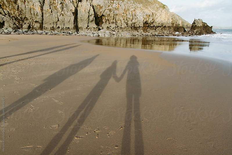 The shadows of people on a beach. Two are holding hands. by Helen Rushbrook for Stocksy United