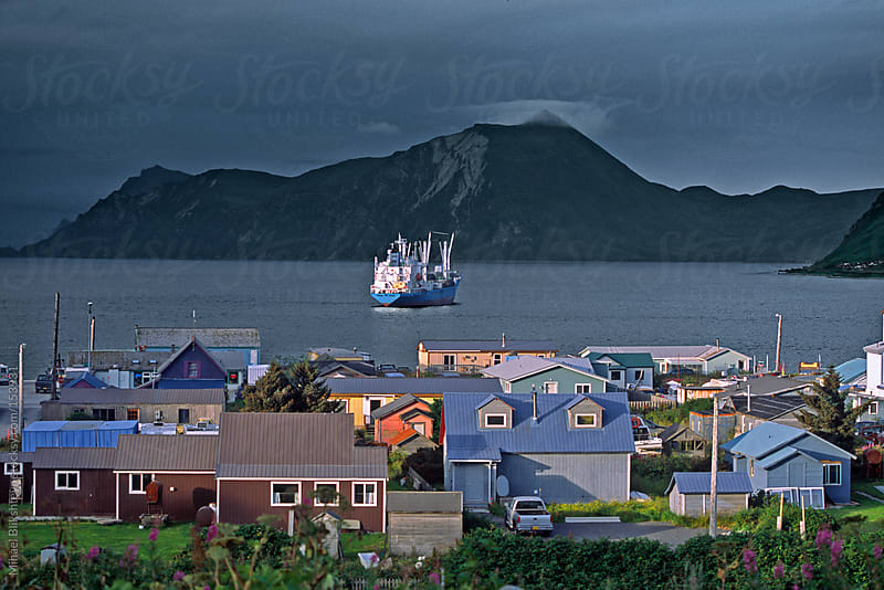 Small coastal town with a fish transport vessel in bay illuminated by sunlight by Mihael Blikshteyn for Stocksy United