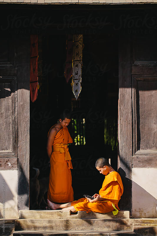 Two young Buddhist monks spending leisure time at the temple entrance by michela ravasio for Stocksy United