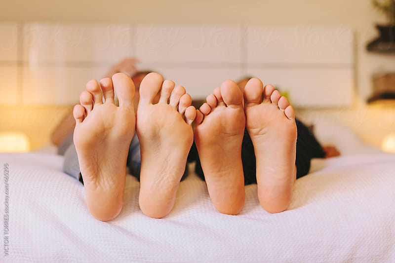 A pair of Women's Feet in Bed by VICTOR TORRES for Stocksy United