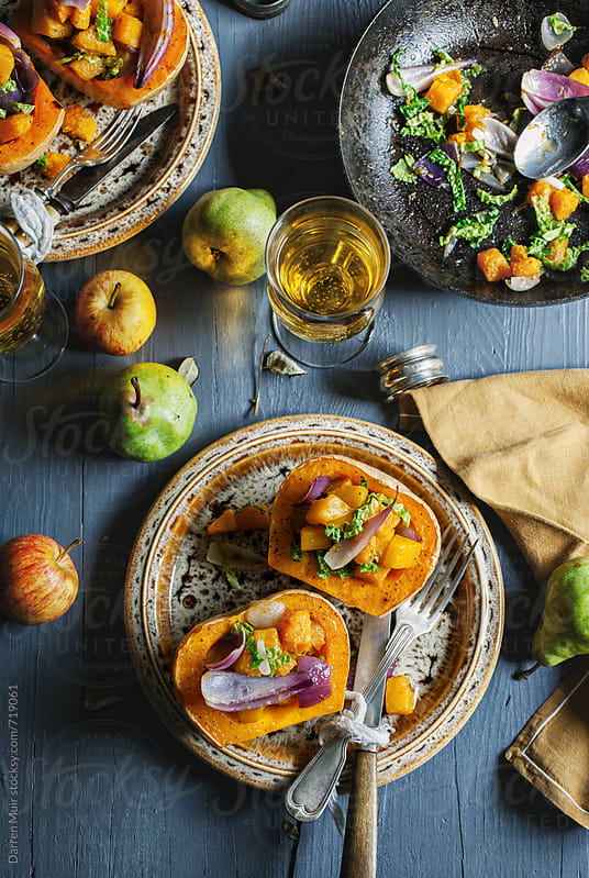 Stuffed roasted squash on a table with fruit and cider. by Darren Muir for Stocksy United