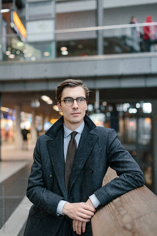 Portrait Of Young Businessman Standing In A Mall by VegterFoto for Stocksy United