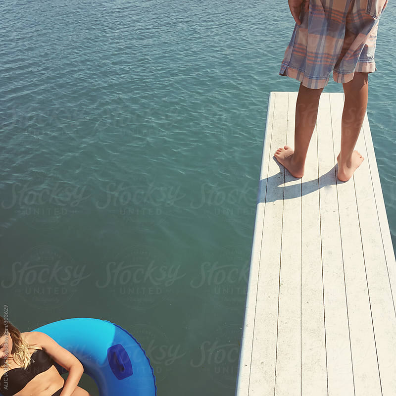 A Boy Standing On A Diving Board And A Girl Floating In The Water Below by ALICIA BOCK for Stocksy United