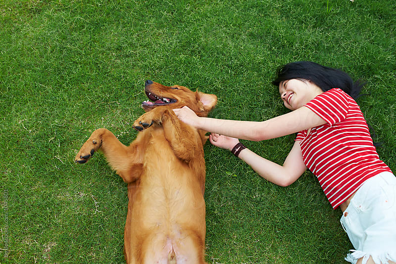 happy young woman having fun with her dog outdoor by Bo Bo for Stocksy United