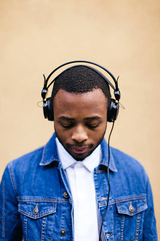 Portrait of a man listening music with headphone. by BONNINSTUDIO for Stocksy United