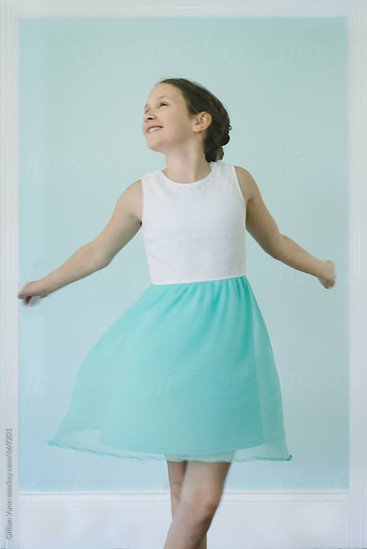 girl twirling in a pretty blue dress against a blue wall, she is framed like a polaroid by Gillian Vann for Stocksy United