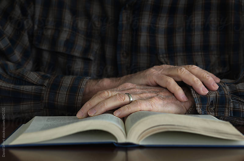 Hands of a senior man, who is  wearing a wedding ring, on the pages of an open book. by David Smart for Stocksy United