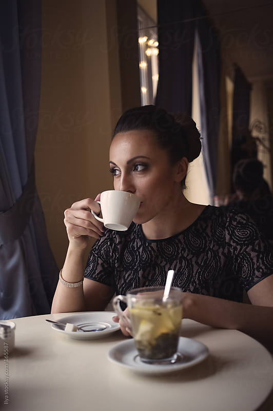 Woman in cafe with a cup of coffee by Ilya for Stocksy United