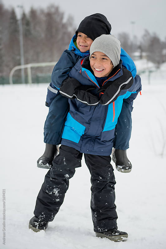 brothers having fun in the snow  by Andreas Gradin for Stocksy United
