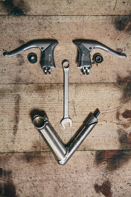 Bicycle spare parts shaped like a smiling face by Lior + Lone for Stocksy United