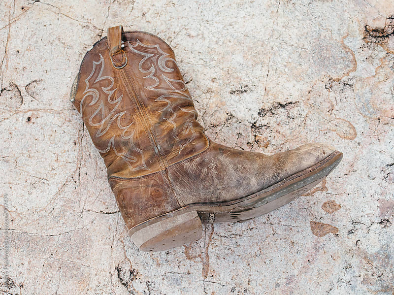 Well worn cowboy boot on rock, Texas. by Jeremy Pawlowski for Stocksy United