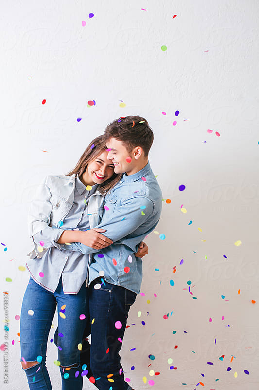 Young lovers enjoying as confetti falls from above. by BONNINSTUDIO for Stocksy United