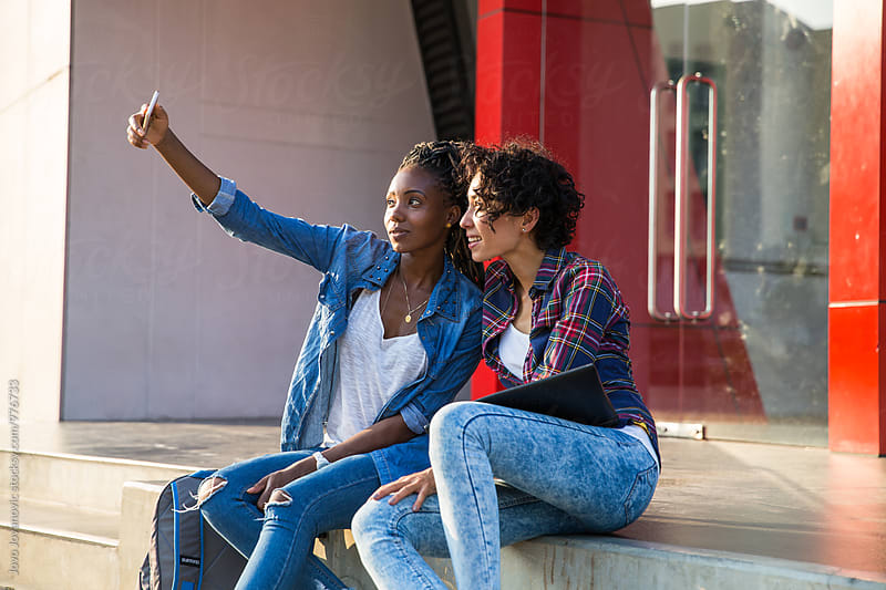 Girlfriends taking a selfie in campus  by Jovo Jovanovic for Stocksy United