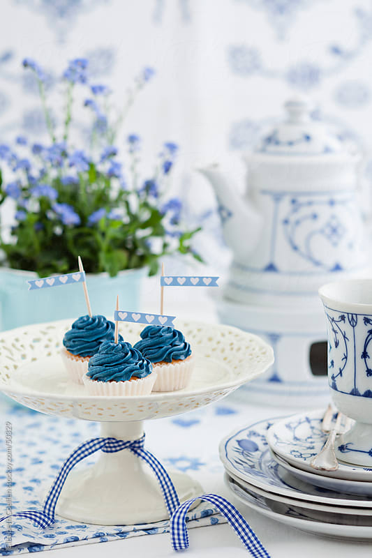 Coffee table with mini cupcakes with blue cream cheese frosting with indian blue porcelain by Elisabeth Coelfen for Stocksy United
