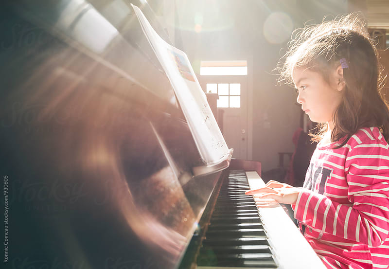 Little Girl Playing Piano by Ronnie Comeau for Stocksy United