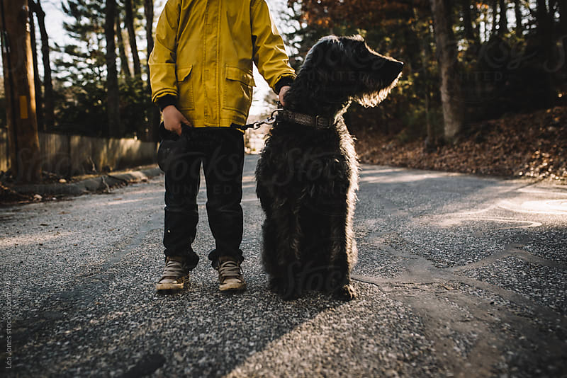 little boy walking  a black dog by Léa Jones for Stocksy United