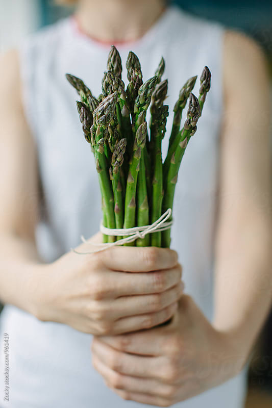 Woman holding asparagus by Zocky for Stocksy United