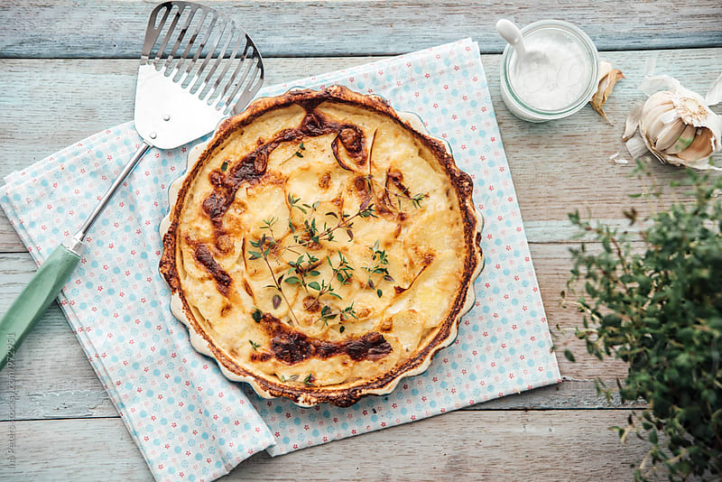 Food: gratinated potatos with thyme in a round dish by Ina Peters for Stocksy United