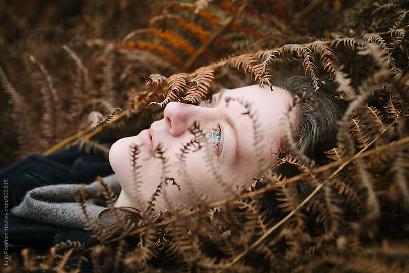 Beautiful woman lying on her back among autumn fern by Julia Forsman for Stocksy United