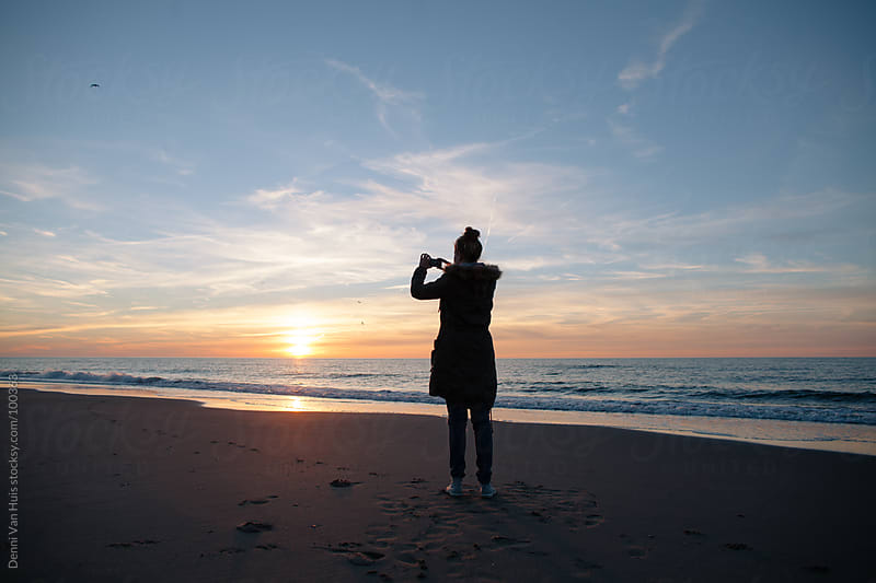Woman taking a photo of the sunset with her phone on the beach by Denni Van Huis for Stocksy United