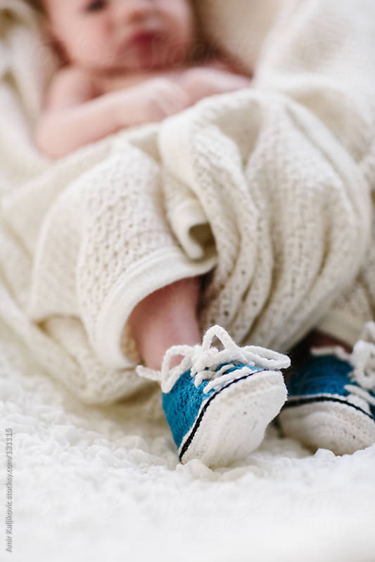 First pair of tiny blue baby booties by Amir Kaljikovic for Stocksy United
