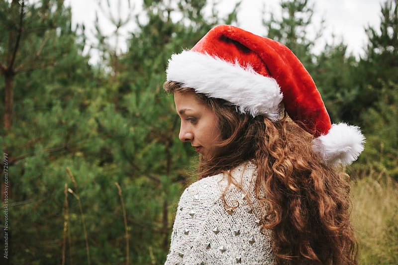Young woman with christmas hat shot from behind, outdoors by Aleksandar Novoselski for Stocksy United