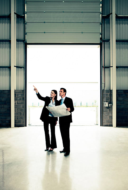 Business people looking at plans in empty warehouse. by Hugh Sitton for Stocksy United