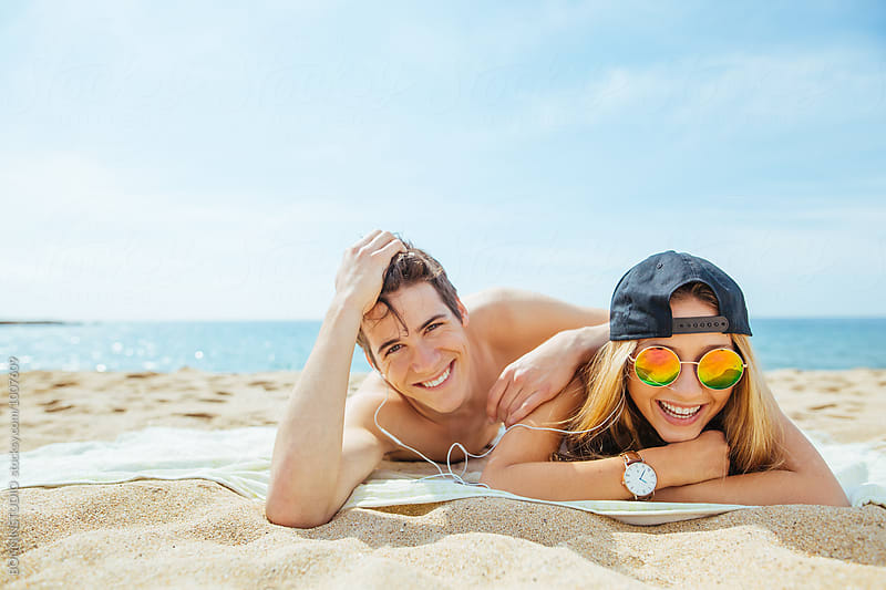 Portrait of a happy teenage couple tanning on the beach. by BONNINSTUDIO for Stocksy United
